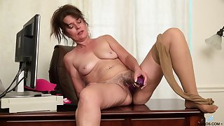 Grown up Shelby Gleam is alone in the office and plays with her favorite dildo